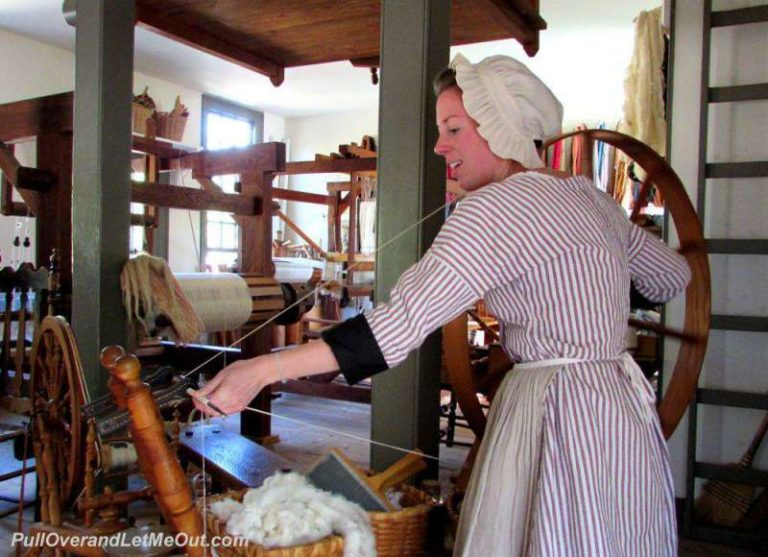 A costumed interpreter working with a spinning wheel in Colonial Williamsburg