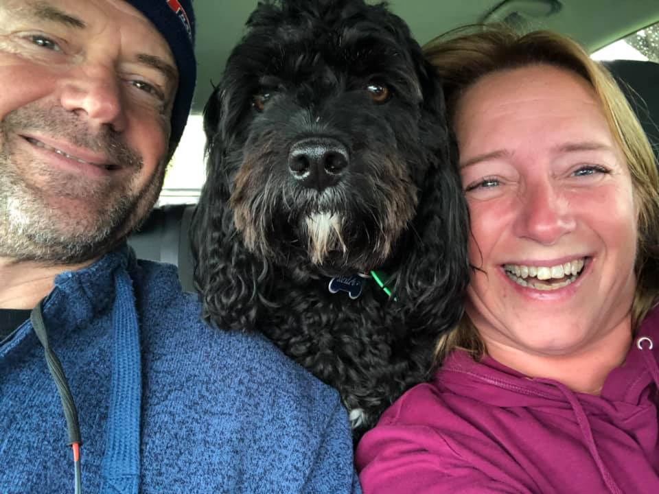 Two people with a large black dog in a car. Trusted House Sitters PullOverAndLetMeOut.com