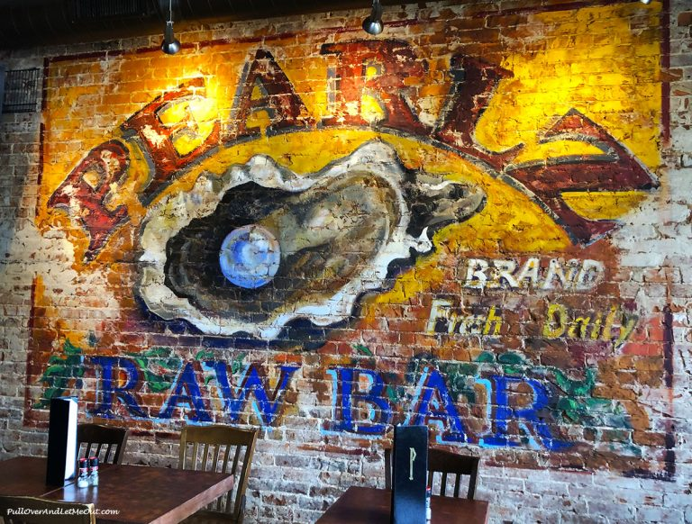 Pearlz restaurant art on exposed brick wall. PullOverAndLetMeOut
