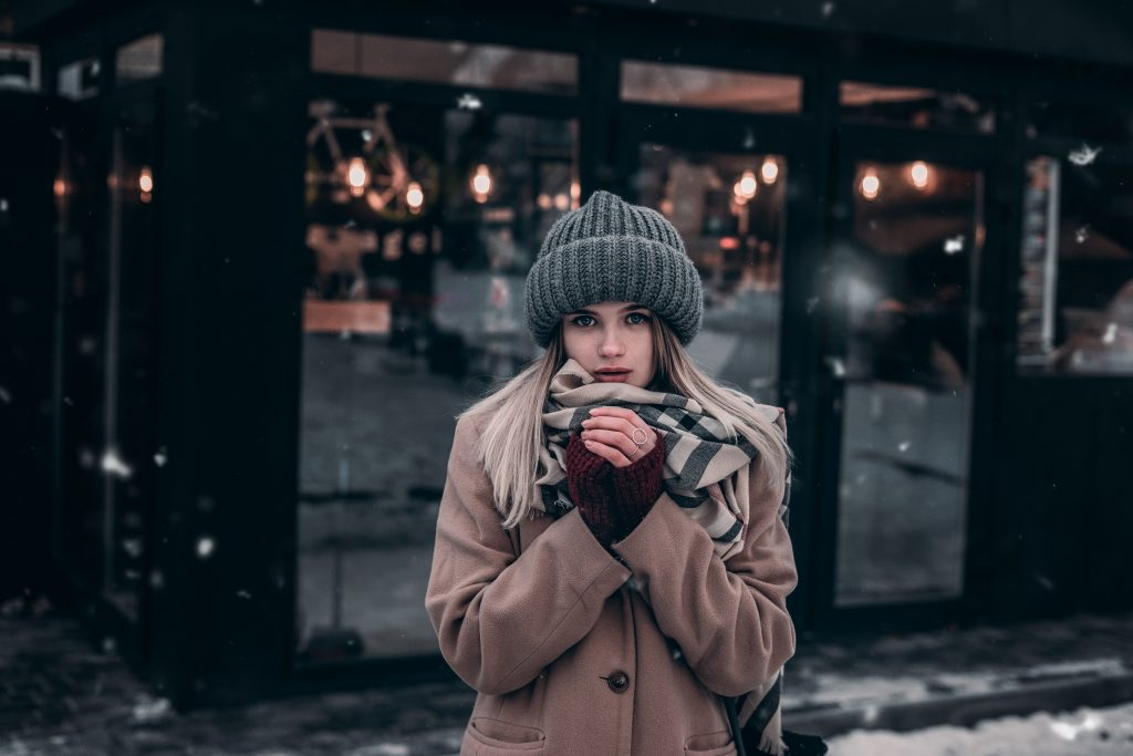 woman in winter clothing sipping hot drink