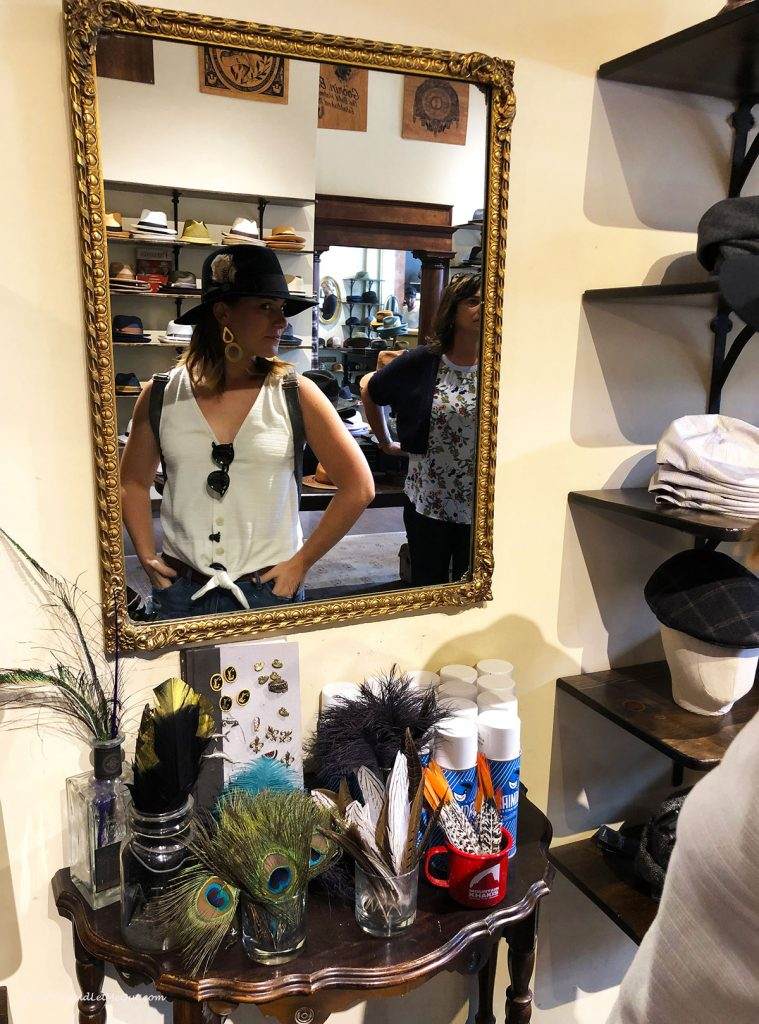 A woman in a hat looking in the mirro. PullOverAndLetMeOut