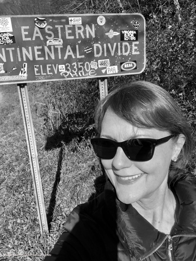 Anna Marie in front of the sign for the Eastern Continental Divide.