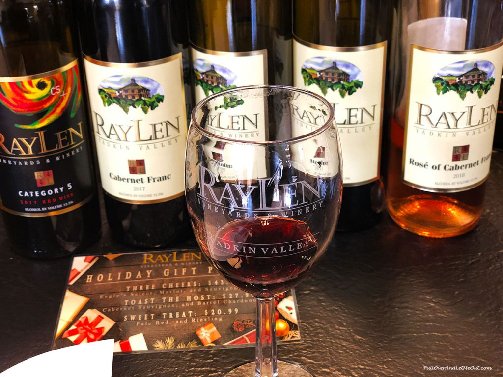 A glass of wine in front of several RayLen Wine bottles. PullOverAndLetMeOut
