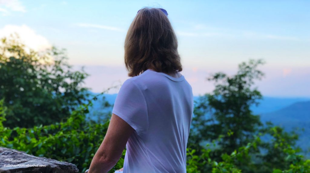 Woman's back to camera as she looks at the mountains.
