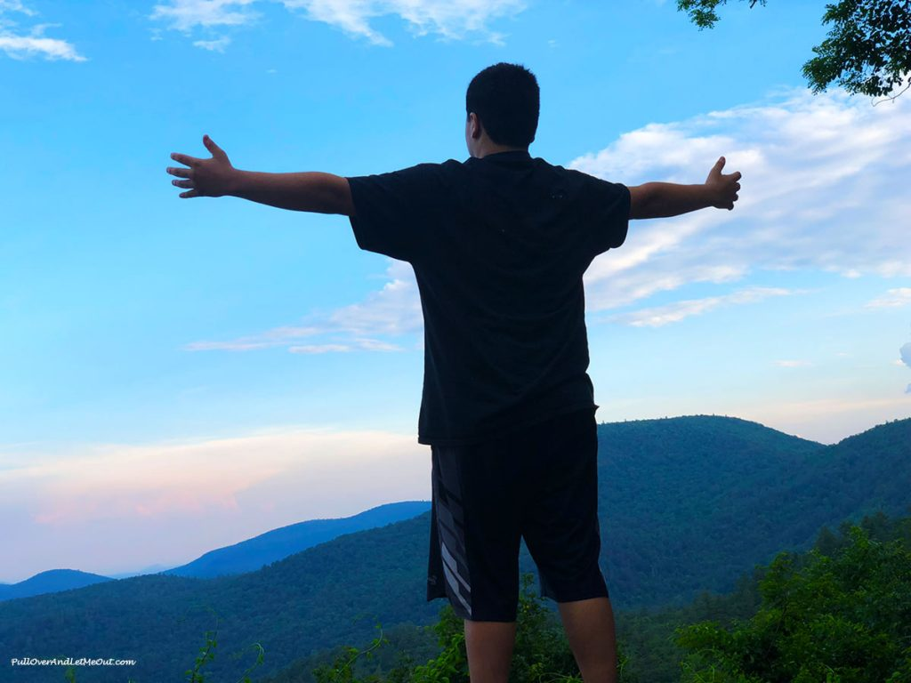 Guy with arms spread looking at mountains