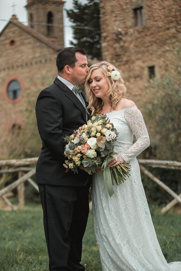 A bride and groom in front of a Tuscan castle