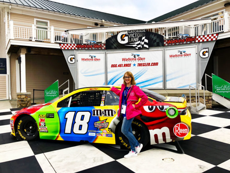 Woman standing in front of NASCAR number 18 M&M car