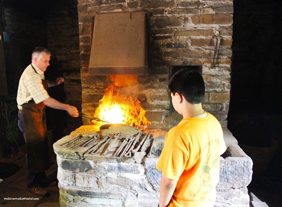 A boy watching a blacksmith working at Bunratty Castle and Folk Park