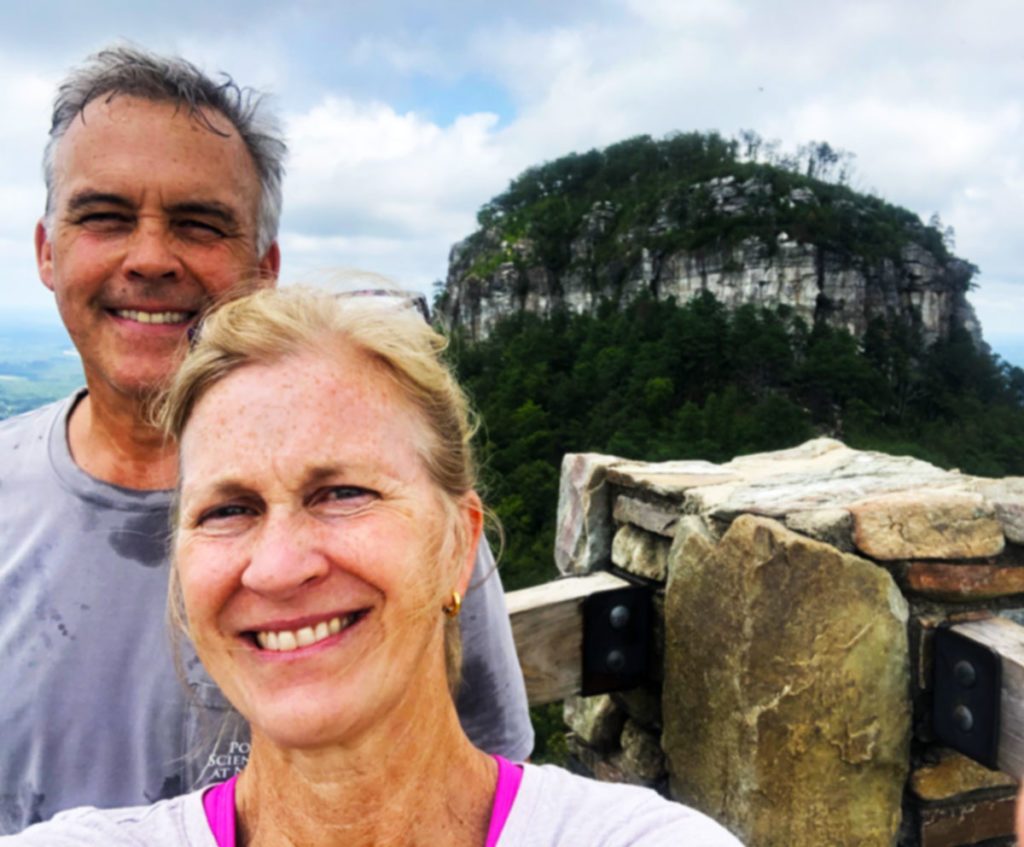 A man and woman taking a selfie in front of Pilot Mountain