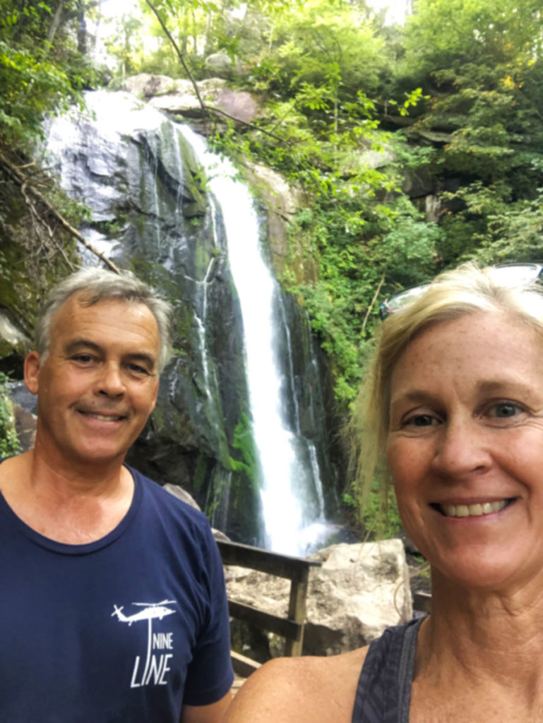 man and a woman standing in front of a waterfall