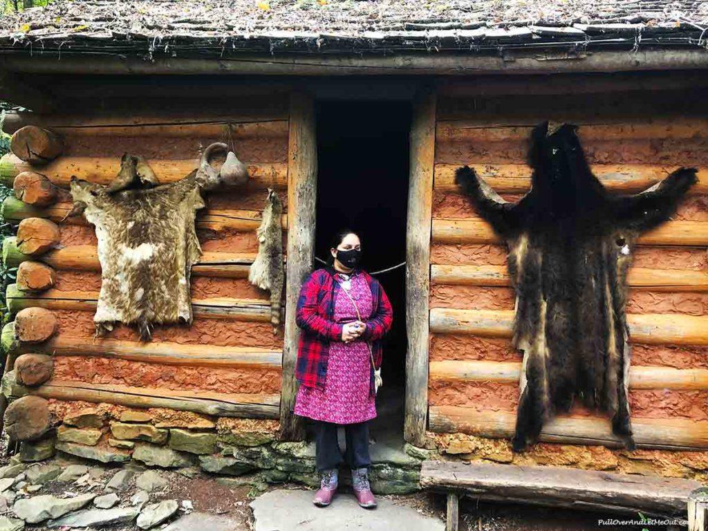 Cherokee tour guide in front of log cabin in Oconaluftee Indian Village Cherokee, NC