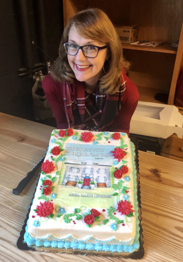 Author Anna Marie Jehorek with a cake decorated with the book cover of The House with the Georgian Door