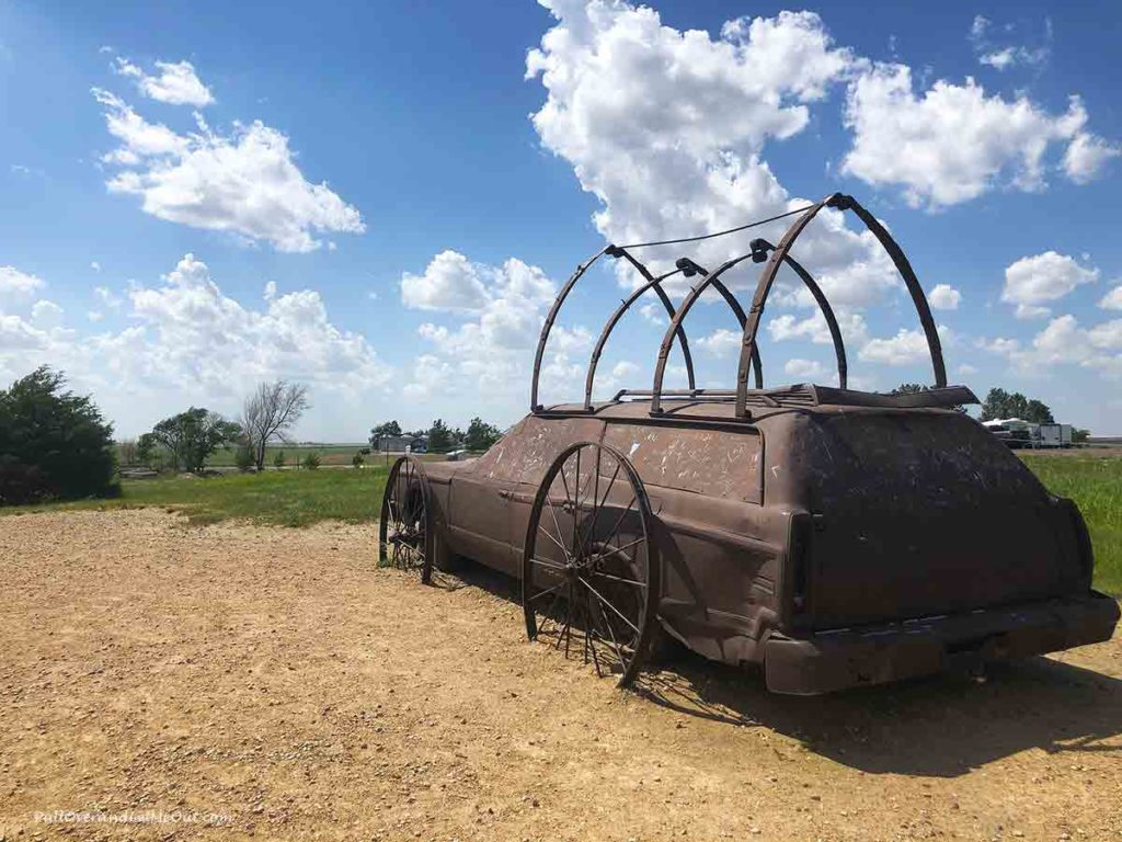 A scupture of a covered wagon made from an old station wagon