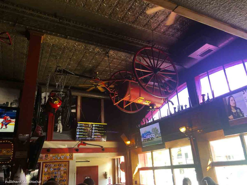 old fire engine hanging on the ceiling of a fire house