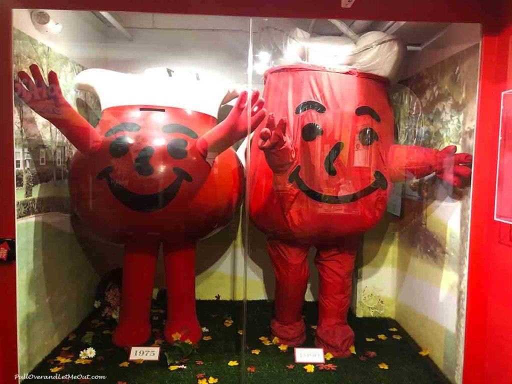 Two Kool-Aid Man costumes inside a display case in a museum