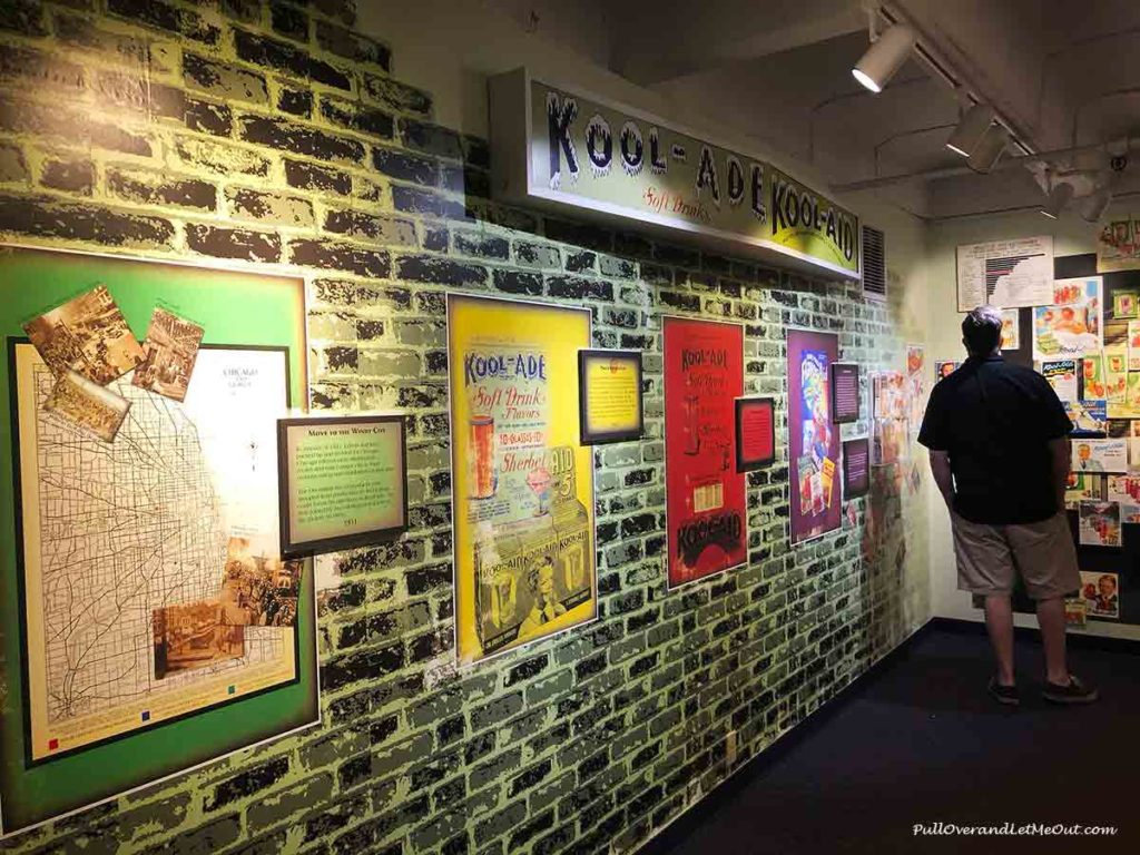 A man looking at a wall exhibit filled with Kool-Aid memorbilia