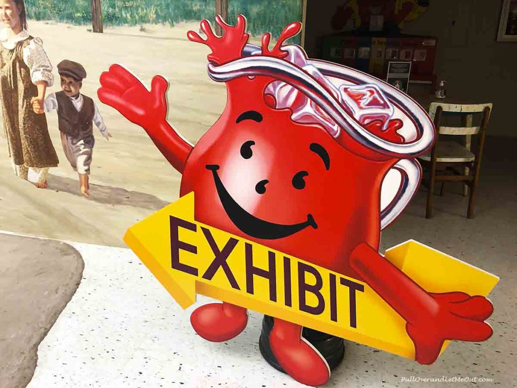 """The Kool-Aid Man sign holding an arrow that says """"exhibit"""""""