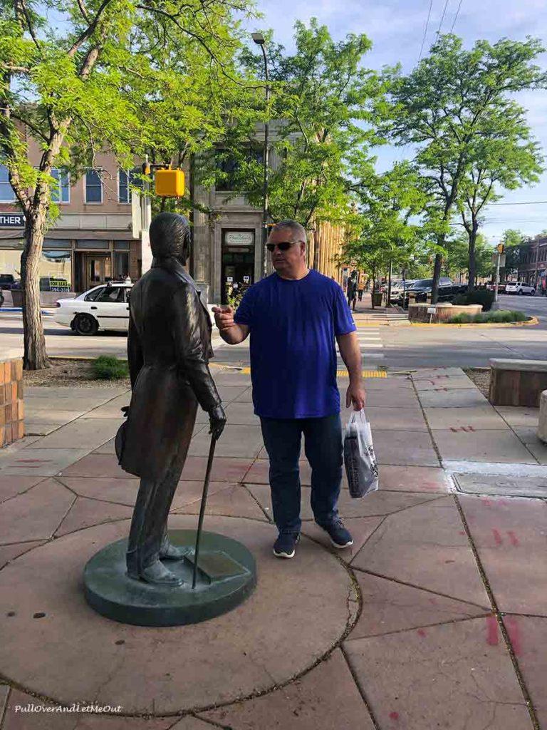 man looking at a bronze statue of John Quincy Adams