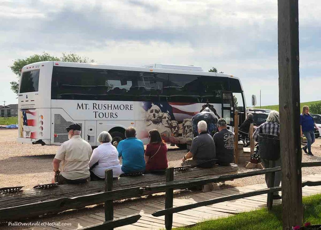 people sitting on a bench in front of a tour bus